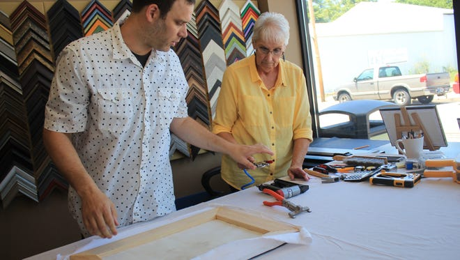 Joshua Davidson and his mother Londa Davidson frame a cloth canvas. Shutterbug Printing Services recently added custom framing as an option for their prints.
