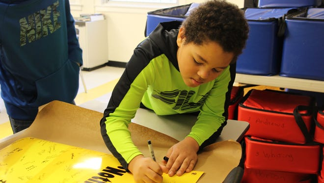 Windsor seventh grader Christian Rogers signs a banner for students at Marjory Stoneman Douglas High School in Florida.