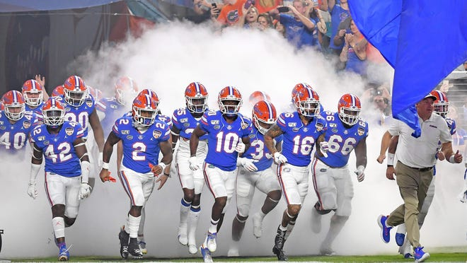 Imagine if Florida coach Dan Mullen, shown here leading his team onto the field for last December's Orange Bowl, were to lead the charge against coronavirus along with his fellow state college football coaches.