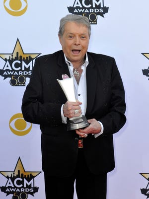 Mickey Gilley with an award on the red carpet of the ACM awards.