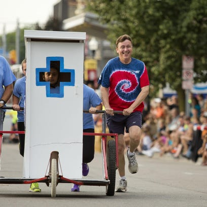 Team CSB pushes their outhouse during the Bologna Festival outhouse races last year in Yale.