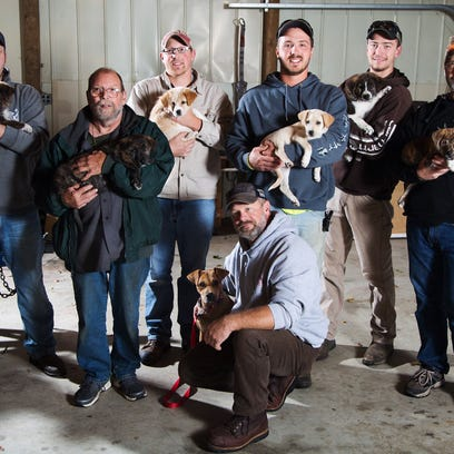 Eight men, a mama dog and her litter,