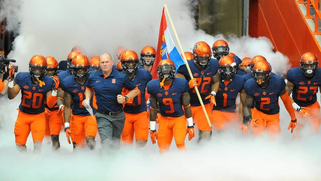 Syracuse players and coaches take the field for a game last September.