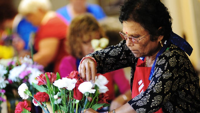 Jolly Sahu of Madison, joins other volunteers at Hospice Ministries in Ridgeland to create flower arragements for residents. Volunteers create and deliver arrandements throughout the building twice a week, made with donated flowers from Kroger and Fresh Market.