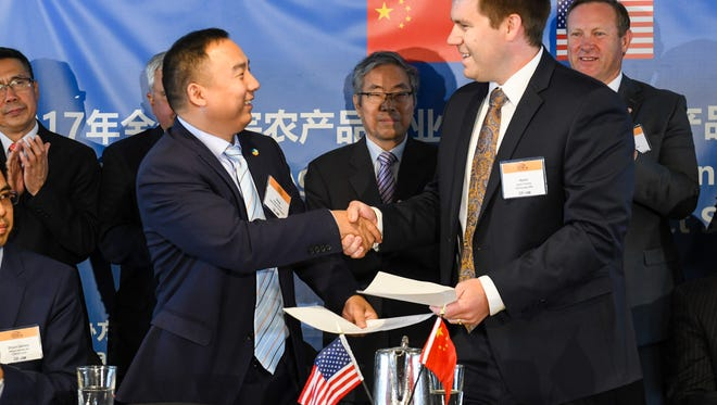 Wang Yunchao, general manager of COFCO Oils and Fats, shakes hands with Aaron Christie, of CHS Europe SARL, after signing purchase agreements for U.S. soybeans Thursday in Des Moines. Chinese buyers agreed to purchase more than $5 billion worth of soybeans today leading up to a historic Iowa agricultural trade mission to the country next week.