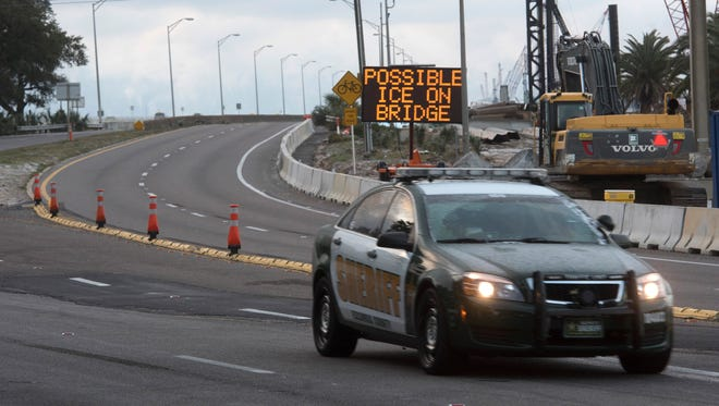 Law enforcement officials patrol the Pensacola Bay Bridge after closing the structure over icing concerns, Wednesday Jan.17, 2018.
