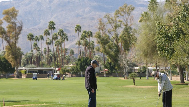 Golfers putt on the 9th green at Shadow Mountain Golf Club in Palm Desert, February 22, 2018.