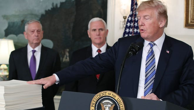 President Donald Trump gestures to the $1.3 trillion spending bill passed by Congress early Friday, with Vice President Mike Pence, center, and Defense Secretary Jim Mattis, left, in the Diplomatic Room of the White House on March 23.