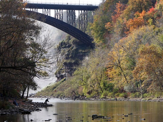 With the Driving Park Bridge looming up behind, a fisherman casts out from a point while fishing the Genesee River near the Lower Falls in this 2013 file photo.