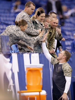 Army Spc. Denise Duggan  high fives punter Pat McAfee before the Colts  game against the Tennessee Titans on Nov. 20 at Lucas Oil Stadium.