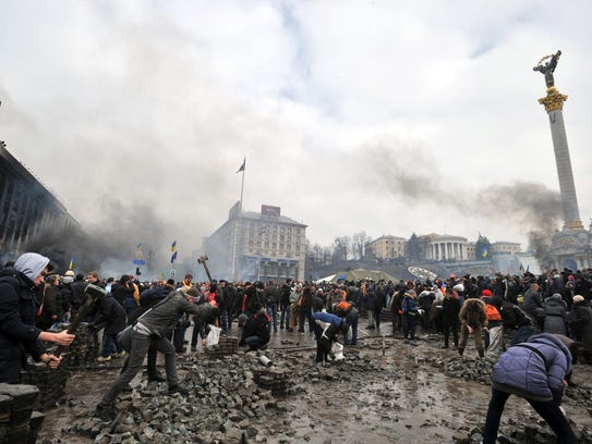 Anti-government protesters dig up cobblestones to use them as rocks against riot police on Kiev's Independence square on February 19, 2014.