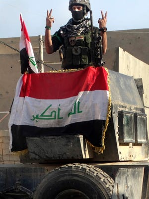 An Iraqi soldier flashes the victory sign after entering the government complex in central Ramadi, 70 miles (115 kilometers) west of Baghdad, Iraq, Monday, Dec. 28, 2015. Iraqi military forces on Monday retook a strategic government complex in the city of Ramadi from Islamic State militants who have occupied the city since May. (AP Photo/Osama Sami)