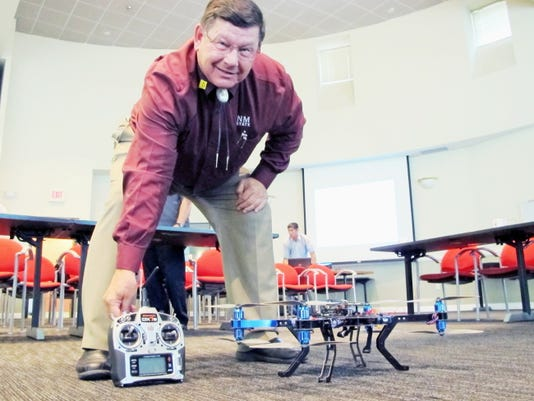Dennis Zaklan, deputy director of New Mexico State University's Unmanned Aircraft Systems Flight Test Center, poses for a photo with the controls for one of the university's drones following a legislative committee meeting in Albuquerque Monday.