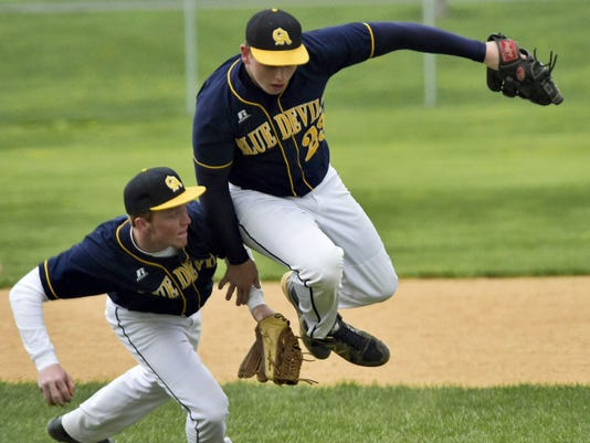 Austin Branchman, left, controls a fielded ball as teammate Matt Kline leaps away from the throw to first base during the West Perry game Monday. The Mustangs won 6-0.