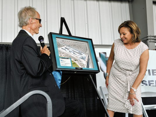 Twin Cities Services' owner Ed Hazelton, left, presents a framed photograph of his business to New Mexico Gov. Susana Martinez on Friday as part of a ribbon-cutting ceremony to mark the expansion of his logistics facility.