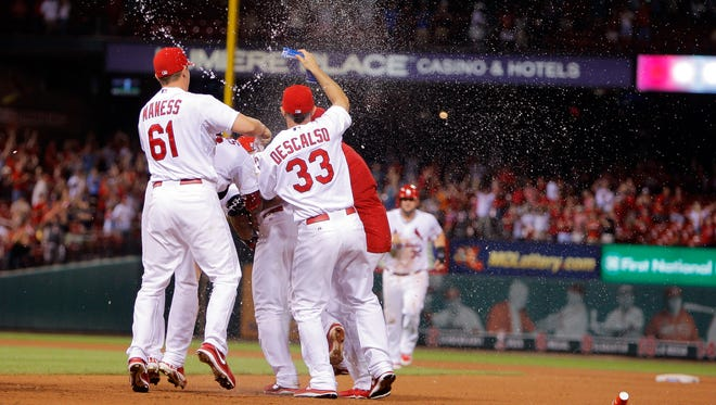 St. Louis Cardinals' Seth Maness, left, and Daniel Descalso, right, join other members of the team as they pour water on Jhonny Peralta after he hit a walk off RBI single during the tenth inning of a baseball game against the Cincinnati Reds, Monday.