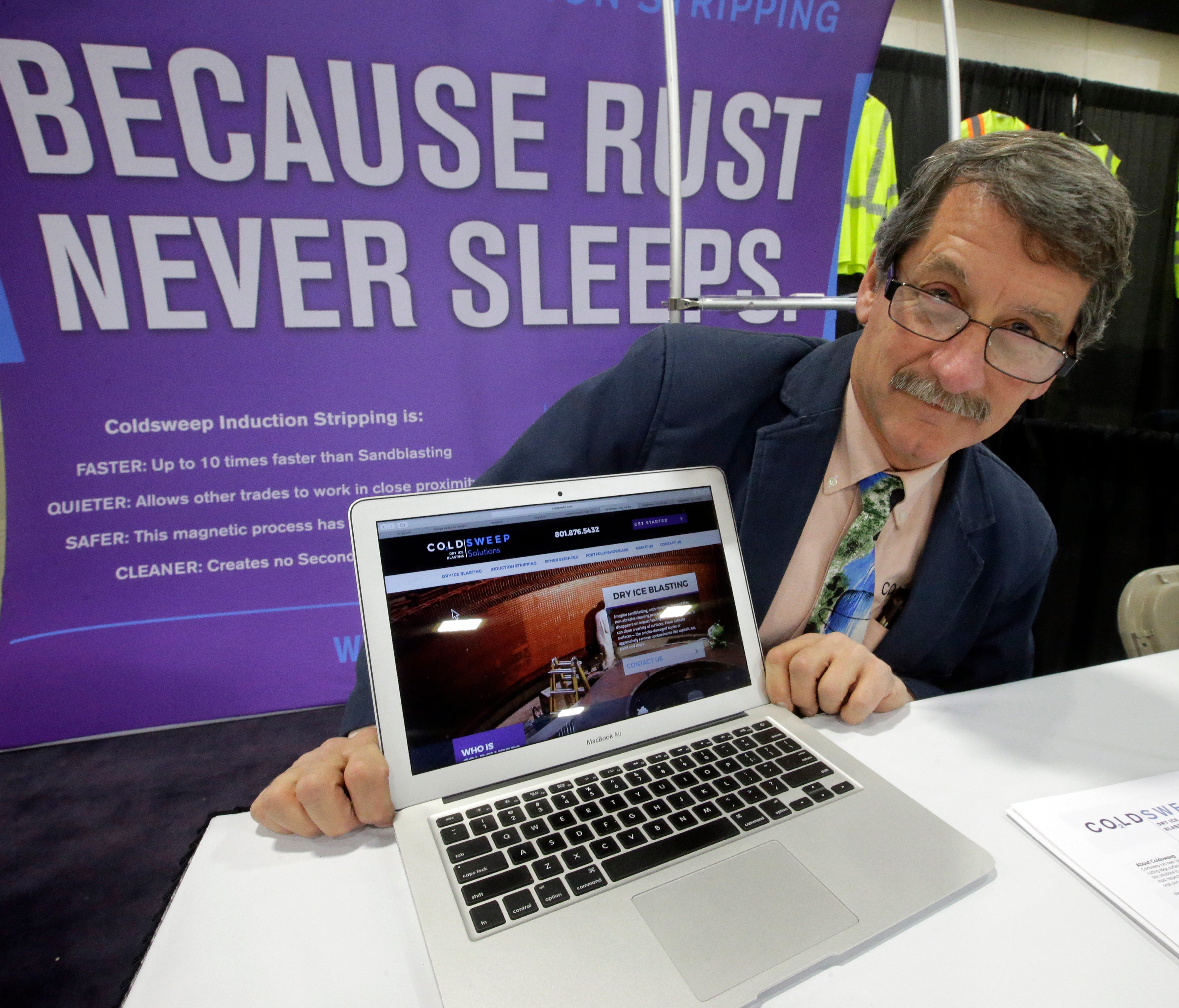 Randell Heath poses next to a laptop displaying his company's website, in Sandy, Utah. Heath's sandblasting company, near Salt Lake City, had its website hacked and turned into a store selling Viagra and Cialis.
