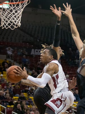 New Mexico State's AJ Harris splits two Northern New Mexico defenders for an acrobatic bucket Tuesday night at the Pan American Center.