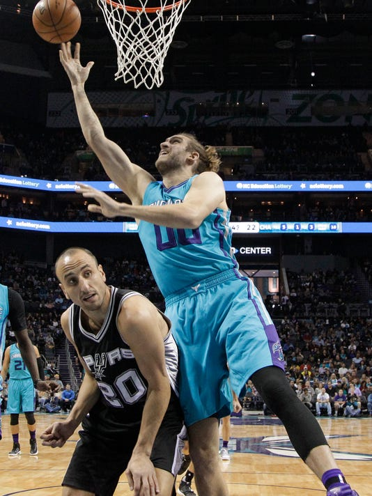 Charlotte Hornets' Spencer Hawes (00) shoots over San Antonio Spurs' Manu Ginobili (20) during the first half of an NBA basketball game in Charlotte, N.C., Wednesday, Nov. 23, 2016. (AP Photo/Chuck Burton)