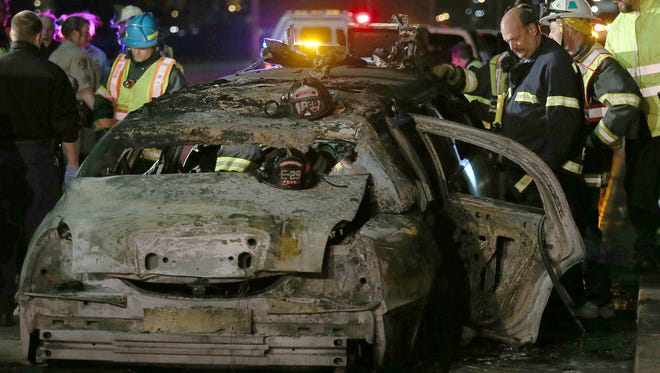 San Mateo County firefighters and California Highway Patrol personnel investigate the scene of a limousine fire on the San Mateo-Hayward Bridge in Foster City, Calif., on May 4.