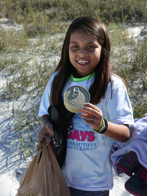 Fernanza Guerrero, 9, from Avalon Elementary, found a full can of cat food in the sea oats.