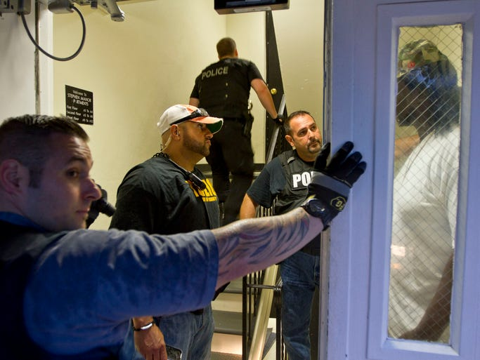 Antonio Martinez, center, and A.J. Bercovicz, second from right, both of Asbury Park Police Department, question a suspect in a foyer of Stephen Manor Apartments. The Asbury Park Police Department along with members of the Monmouth County Sheriff's Department, FBI, and other local agencies sweep the streets in an effort to arrest and detain law breakers. Asbury Park, NJ Friday, June 13, 2014