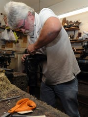Robert Cook works on a pair of boots Monday at Cook's Shoe Repair workshop in Bob's Bootery in downtown Chillicothe.
