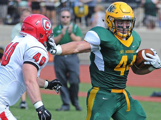 St. Norbert College running back Brad Boockmeier (44) stiff arms linebacker Greg Money (40) to score a touchdown against Carthage College Saturday at Donald J. Schneider Stadium.