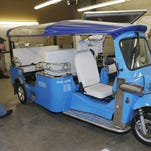 In this photo taken Friday, Feb. 27, 2015, a worker checks the roof on an electric Tuk-Tuk being prepared for export at the Denver eTuk factory in northeast Denver.