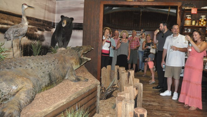 Guests toast Big Joe with Champagne during the unveiling of the new exhibit at Everglades Wonder Gardens.