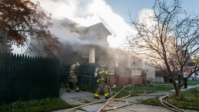 Firefighters circle around the house as they fight the fire Monday, Nov. 7 at 432 12th Street in Port Huron.