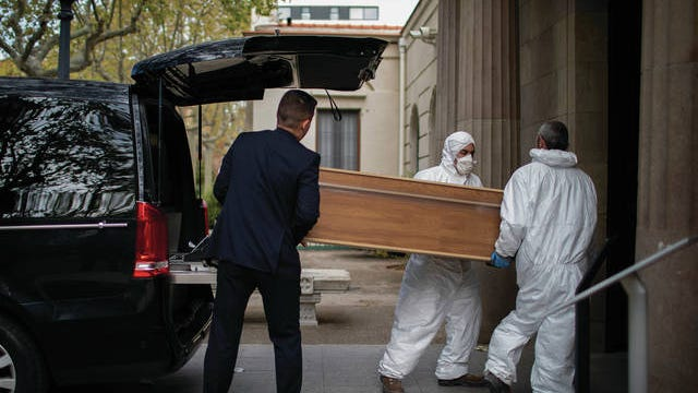 Undertakers carry a coffin for a burial at a Barcelona cemetery during the coronavirus outbreak, in Spain, Friday. The new coronavirus causes mild or moderate symptoms for most people, but for some, especially older adults and people with existing health problems, it can cause more severe illness or death.