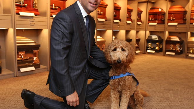 Matthew Fiorillo, owner of the Ballard-Durand Funeral Home in White Plains, with therapy dog Lulu.