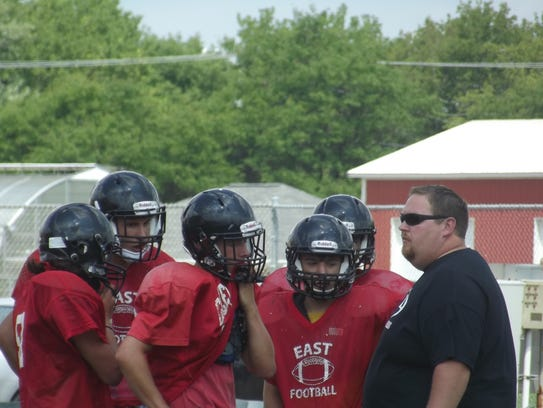 Green Bay East coach Brian Nast talks over a play with
