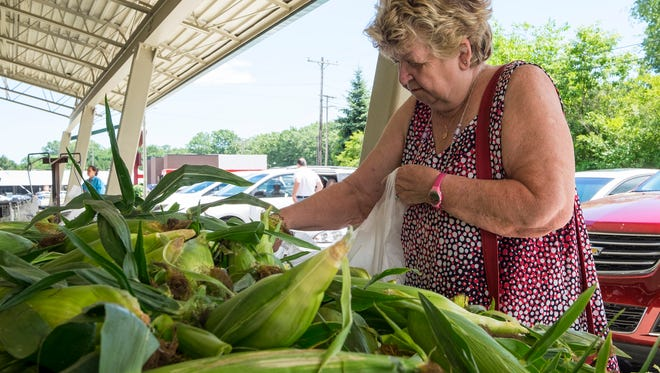 Loretta Parish buys ears of corn Tuesday, July 17, 2018 at  Huletts Farm Market. Sweet corn season has started, and the vegetable is showing up in area farmers markets.