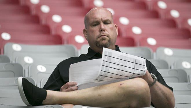 Cardinals general manager Steve Keim looks at paperwork while watching a Cardinals' training camp practice from the seats at University of Phoenix Stadium in Glendale on Wednesday, Aug. 10, 2016.