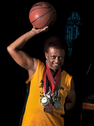 In this Nov. 15, 2017, photo, Patricia Ferguson, 76, shows off her Michigan Spirits uniform and medals won playing basketball at her home in Medford, Ore.