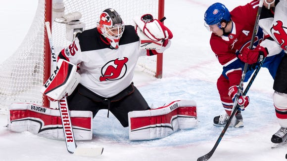 New Jersey Devils goaltender Cory Schneider snags the puck as Montreal Canadiens' Brendan Gallagher looks for a rebound during the first period of an NHL hockey game, Thursday, Dec. 14, 2017 in Montreal. (Paul Chiasson/The Canadian Press via AP)
