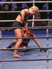 Hannah Goldy, red gloves, and Gillian Robertson, blue gloves, fight each other Friday night during Island Fights 37 at the Pensacola Bay Center.  Goldy won via unanimous decision after the fighters went all three rounds.
