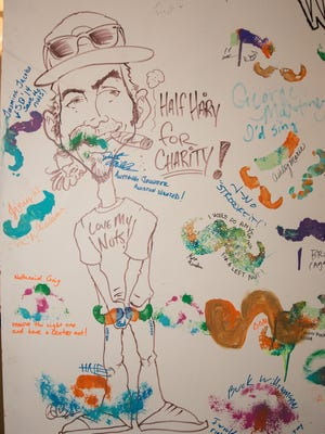 Men with facial hair dabbed their beards and mustaches with water-based paint and filled up a canvas outside of Wildrid's Barber and Fine Goods to bring awareness to the fight against testicular cancer during November's Gallery Night.