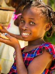 One of the local children smiles while eating her bread. The team passed out bread as a part of Together for Christ Haiti Bread Coalition.
