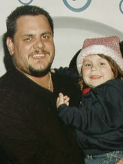 In this undated file photo provided by the family, retired New York City Police Detective James Zadroga holds his daughter Tylerann. In a letter to his father Joseph Zadroga dated Tuesday, Oct. 16, 2007, the New York City medical examiner has ruled that James Zadroga's death was not caused by his exposure to toxic World Trade Center dust while working hundreds of hours at ground zero.