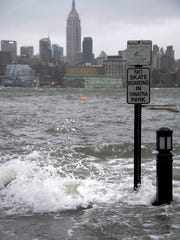 The Hudson River swells and rises over the banks of the Hoboken, N.J. waterfront as Hurricane Sandy approaches on Monday, Oct. 29, 2012. Hurricane Sandy continued on its path Monday, forcing the shutdown of mass transit, schools and financial markets, sending coastal residents fleeing, and threatening a dangerous mix of high winds and soaking rain.