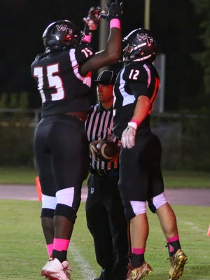 West Florida's Bryant Johnecheck (12) celebrates with Darius Washington (75) after scoring a touchdown against Pensacola High at Woodham Middle School on Friday, October 27, 2017. West Florida clinched the District 1-5A title after beating PHS 33-0.