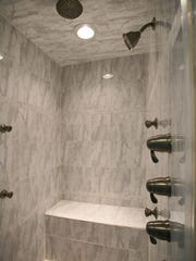 Mater suite bathroom features ceramic floor and tile shower stall.