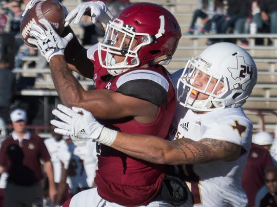NMSU's Royce Caldwell hauls in the pass for a touch down under heavy pressure from Bobcats Javanese O'Roy Saturday afternoon at Aggie Memorial Stadium.