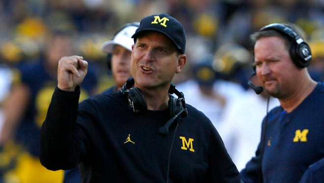 Michigan football coach Jim Harbaugh encourages his players coming off the field after another Michigan score against Penn State football on Saturday, September 24, 2016.
