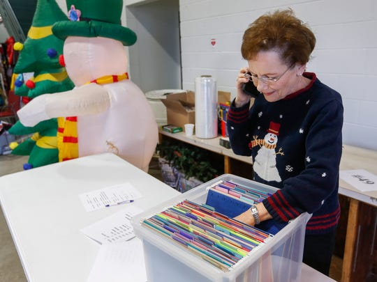 Share Your Christmas coordinator Sheryl Wachter takes a phone call during the gift distribution day at Crosslines on Tuesday, Dec. 19, 2017.