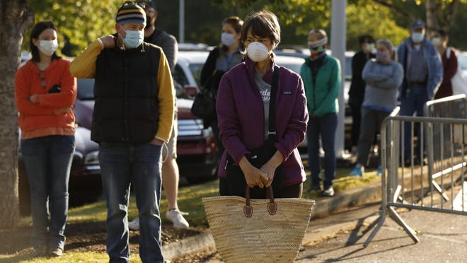 People wait six-feet-apart at opening day of the Athens Farmers Market at Bishop park in Athens, Ga, on Saturday, May 9, 2020. Athens-Clarke commissioners will vote Tuesday night on mandating its citizens to wear masks.