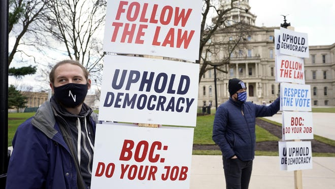 Joscha Weese, left, stands outside the Capitol building during a rally in Lansing, Mich., Saturday, Nov. 14, 2020. Michigan's elections board is scheduled to meet to certify the state's presidential election results Monday.